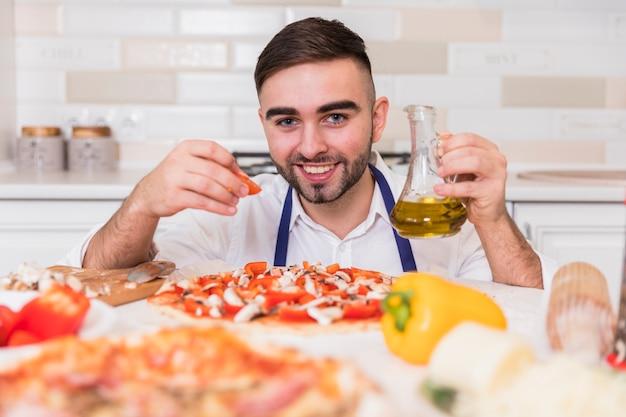 Mann, der pizza mit tomaten kocht
