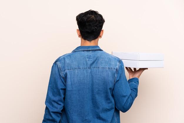 Mann, der pizzas einer kästen über lokalisierter wand hält