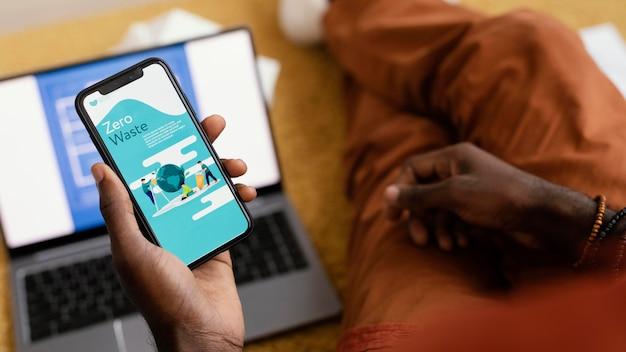 Mann, der pläne macht, haus mit smartphone und laptop zu renovieren