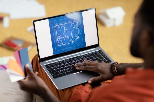 Mann, der pläne macht, haus unter verwendung der farbpalette und des laptops zu renovieren