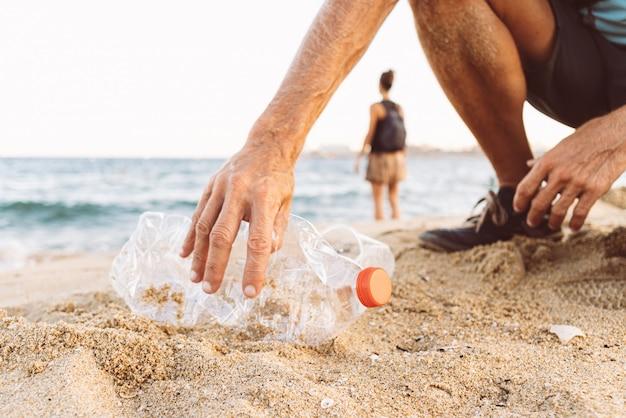 Mann, der plastik am strand aufhebt