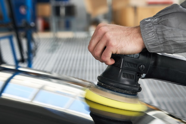 Mann, der polierer verwendet, um schwarze karosserie in der werkstatt zu polieren