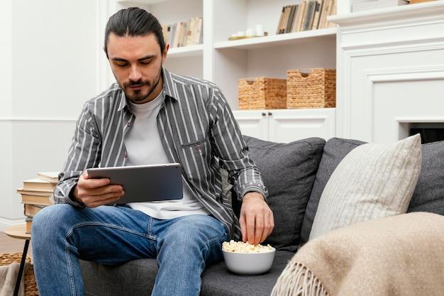Mann, der popcorn isst und eine digitale tablette beobachtet
