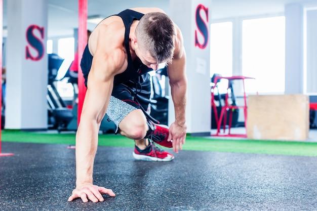 Mann, der push-up in der sporteignungsturnhalle tut