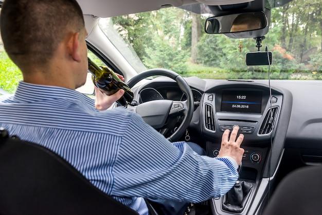 Mann, der radio im auto abstimmt, während er alkoholisches getränk hält
