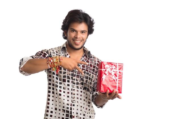 Mann, der rakhi auf seiner hand mit einkaufstüten und geschenkbox zeigt