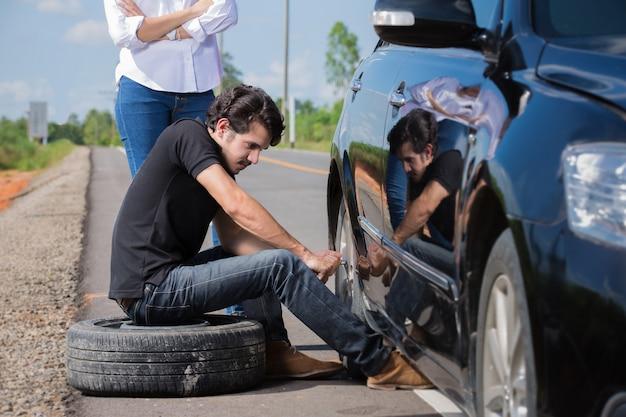 Mann, der reifen ändert, die undicht sind sein auto ist zusammengebrochen