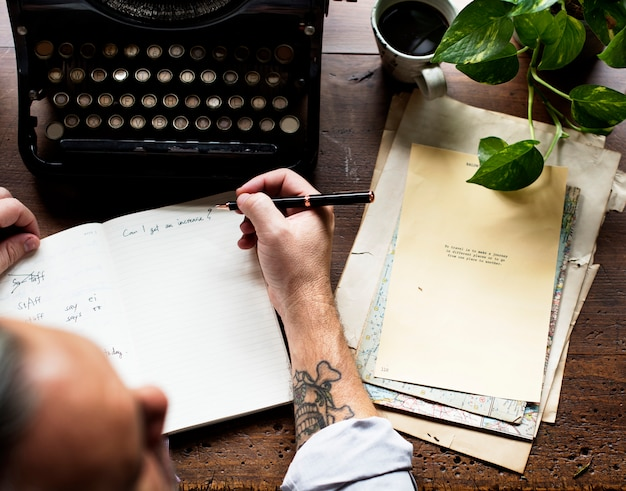 Mann, der retro-schreibmaschine-maschinen-arbeit-verfasser verwendet
