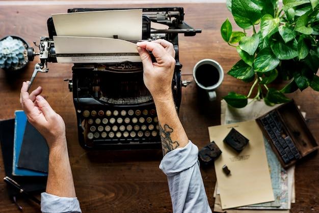 Mann, der retro- schreibmaschinen-maschinen-arbeit-verfasser änderndes papier verwendet