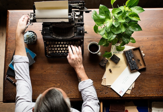 Mann, der retro- schreibmaschinen-maschinen-arbeits-verfasser schreibt