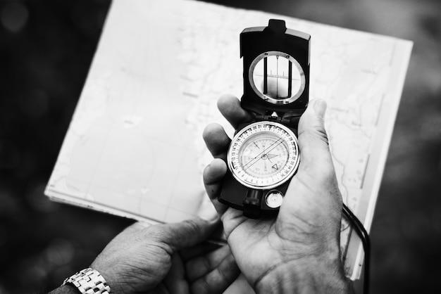 Mann, der richtung auf einen kompass überprüft