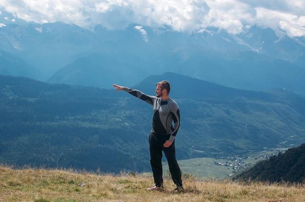 Mann, der richtung mit seinem handand steht in den bergen zeigt