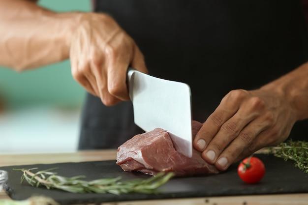 Mann, der rohes fleisch auf schieferplatte in der küche schneidet