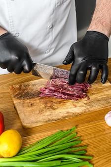 Mann, der rohes rindfleischfleisch schneidet