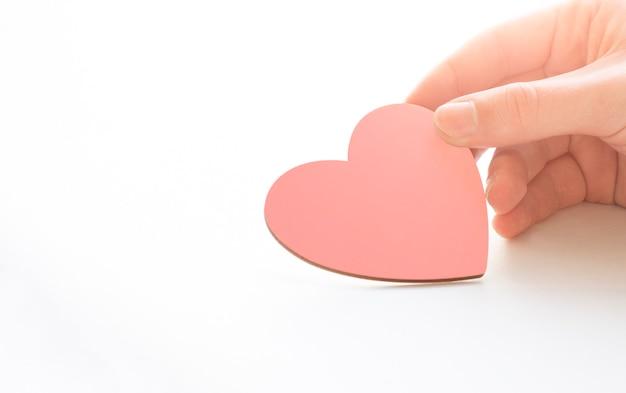 Mann, der rosa handgemachtes herz in händen hält. valentinstag, 14. februar konzept