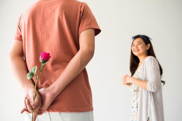 Mann, der rosa rosenblume versteckt, um seine freundin am valentinstag zu überraschen. lächelnde asiatische frau betrachten seinen freund mit kopienraum für text.