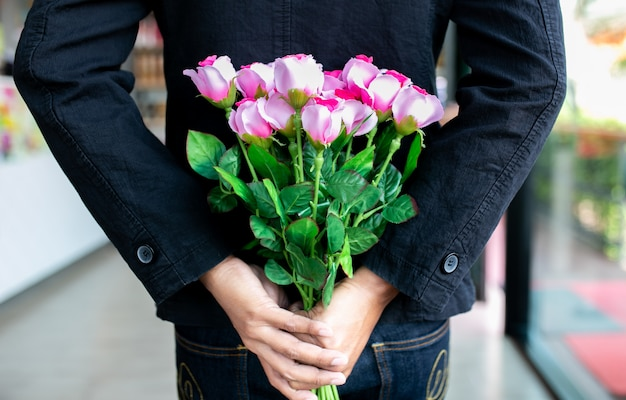 Mann, der rosa rosenstrauß auf rücken hält, überraschung besondere zeit.