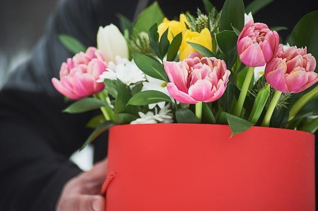 Mann, der rote geschenkbox mit schönem blumenstrauß hält