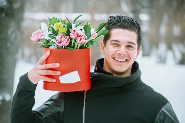 Mann, der rote geschenkbox mit schönem blumenstrauß von blühenden rosa, gelben und weißen tulpen und weißen chrysanthemen mit grünen blättern im freien hält