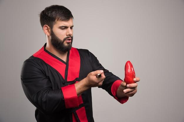 Mann, der roten pfeffer mit messer auf grauer wand hält