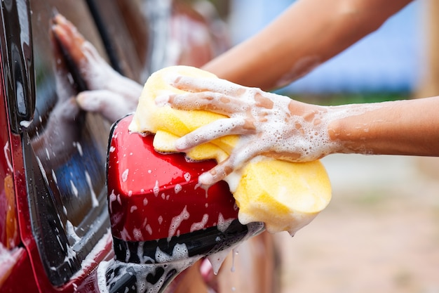 Mann, der rotes auto mit schwamm und seife wäscht