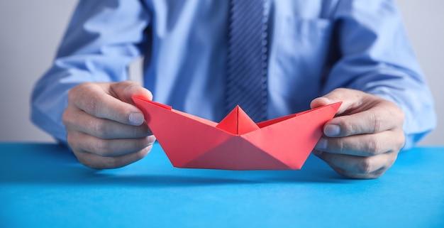 Mann, der rotes origami-papierboot hält.
