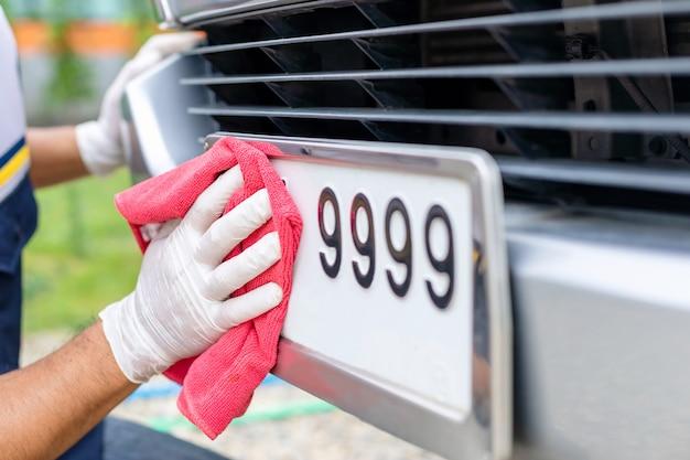 Mann, der rotes tuch verwendet, um vorderes autokennzeichen zu säubern