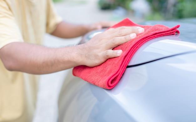 Mann, der rotes tuch zum säubern des suv-autos verwendet