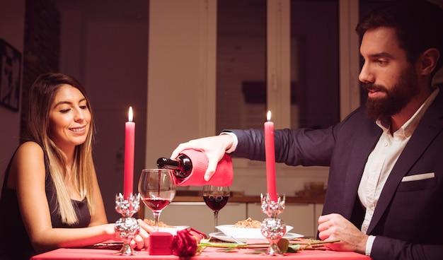 Mann, der rotwein in ein glas frau gießt