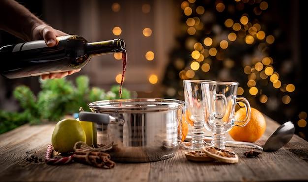 Mann, der rotwein von der flasche in den topf gießt, um zu glühen und aromatisches glühgetränk vorzubereiten
