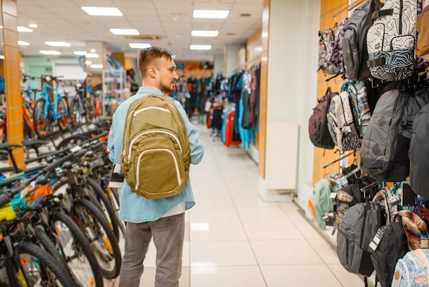 Mann, der rucksack wählt, im sportgeschäft einkauft. extremer lebensstil der sommersaison, aktives freizeitgeschäft, kunden, die touristische ausrüstung kaufen