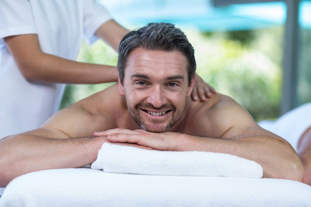 Mann, der rückenmassage vom masseur empfängt