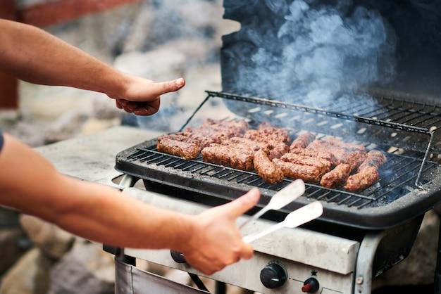 Mann, der rumänisches mititei auf grill kocht