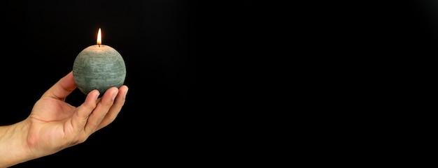 Mann, der runde brennende kerze auf dunklem hintergrund hält