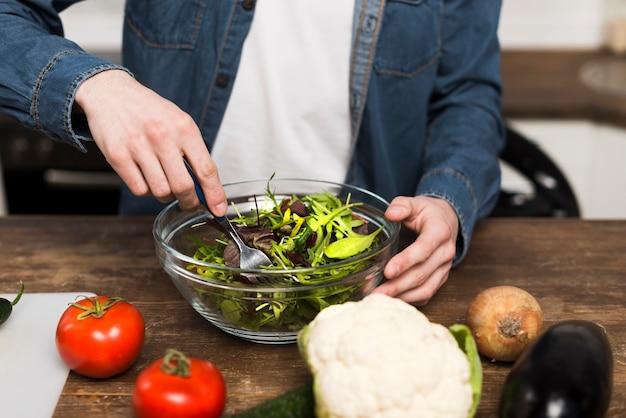Mann, der salat in der küche zubereitet