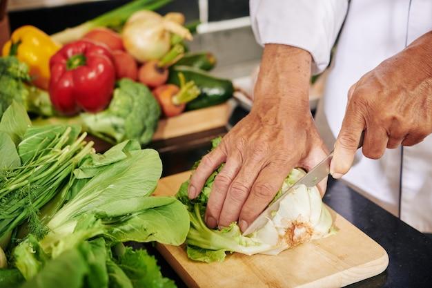 Mann, der salatwurzel abschneidet