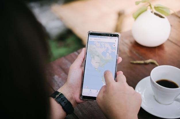 Mann, der samsung smartphone hält und anwendung google maps zum bestimmungsort verwendet