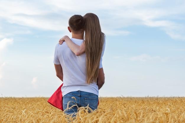 Mann, der sanft seine geliebte im weizenfeld hält. romantische zeit außerhalb
