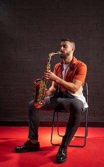 Mann, der saxophon spielt, während er sich hinsetzt