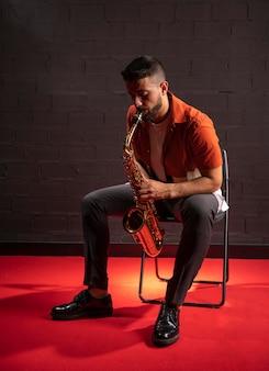 Mann, der saxophon spielt, während er sitzt