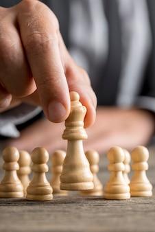 Mann, der schach spielt, das königinstück bewegt, das es in seinen fingern in einer nahaufnahmeansicht anhebt.