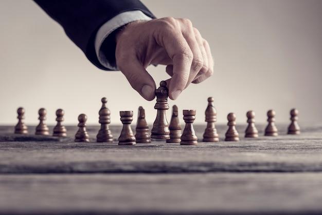 Mann, der schach spielt und die königin bewegt, hebt sie in seinen fingern an