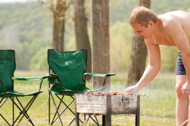 Mann, der schaschlik grillt