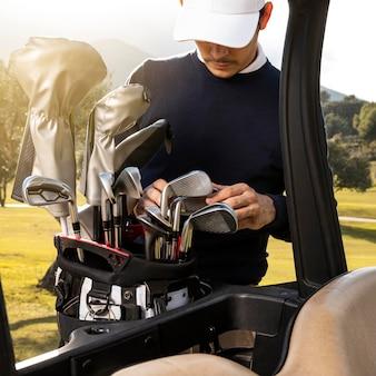 Mann, der schläger in golfwagen setzt