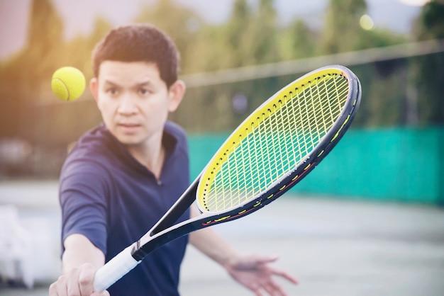 Mann, der schläger ungefähr hält, um einen ball im tennisplatz zu schlagen