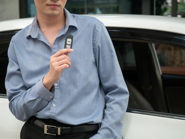 Mann, der schlüssel im modernen autohaus hält. schließen sie herauf hand des kardealers, der dem kunden autoschlüssel gibt