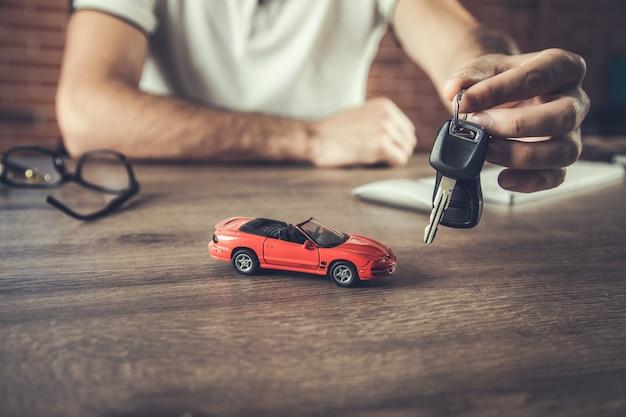 Mann, der schlüssel mit automodell auf tisch hält