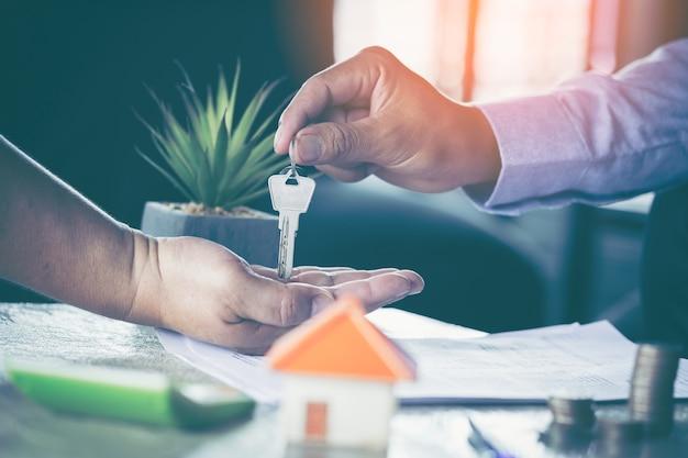 Mann, der schlüssel vom männlichen immobilienmakler während der sitzung nach unterzeichnen des mietleasingvertrages nimmt