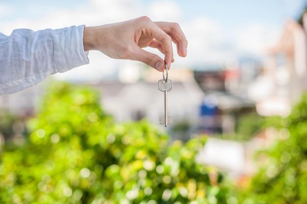 Mann, der schlüssel zum haus auf hintergrund von häusern in der stadt hält. beschäftige dich mit dem immobilienkonzept