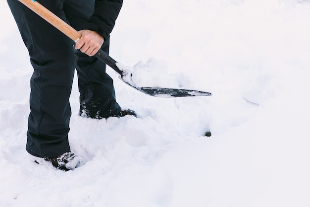 Mann, der schnee aus dem garten seines hauses mit einer schaufel entfernt